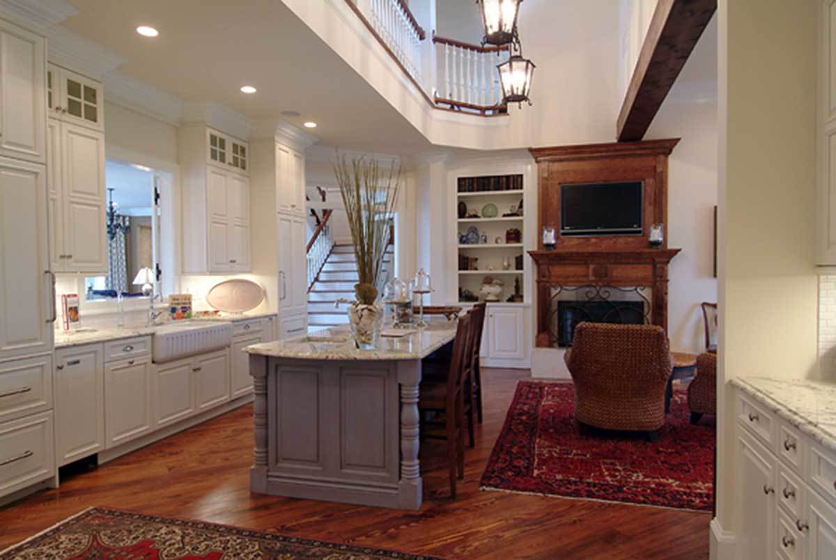 A keeping room complete with wicker chairs, a fireplace, and a wall-mounted TV sits beside the kitchen.