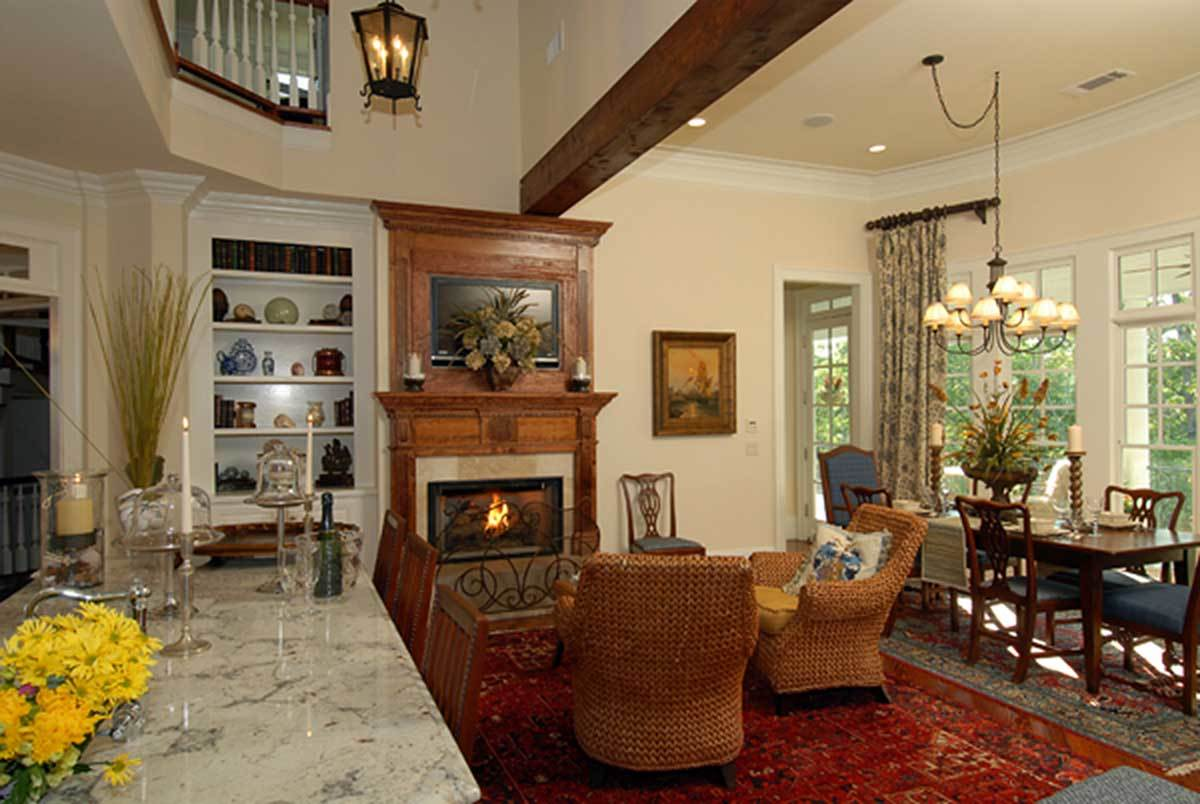 Next to the keeping room is the breakfast nook offering blue cushioned chairs and a rectangular dining table.