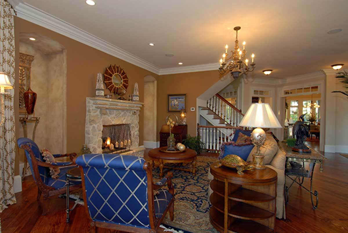 Living room with a skirted beige sofa, blue patterned armchairs, round tables, and a stone fireplace adorned with a red sunburst mirror.