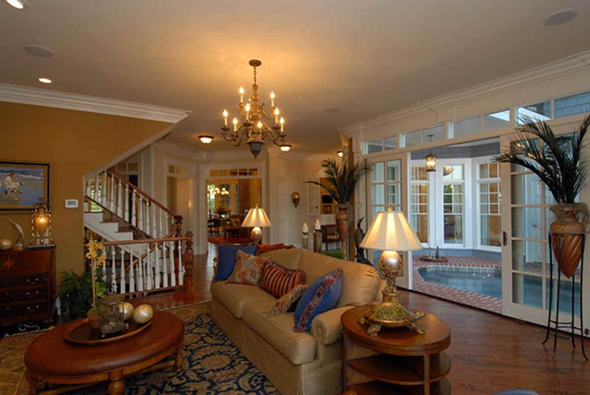 The sliding glass doors behind the beige sofa lead to the rear porch with a garden pool.