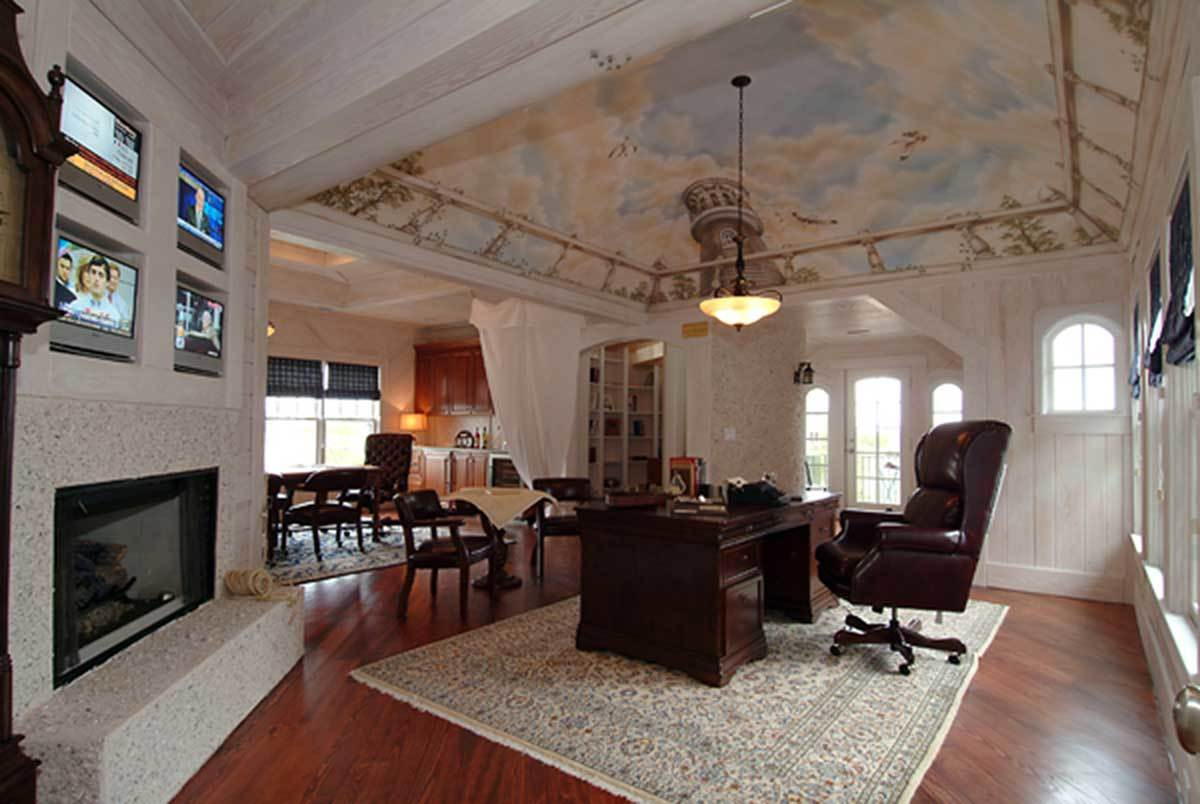 Home office with a corner fireplace, small mounted screens, dark wood and leather furnishings, white beadboard walls, and a stunning tray ceiling adorned with a sky mural.