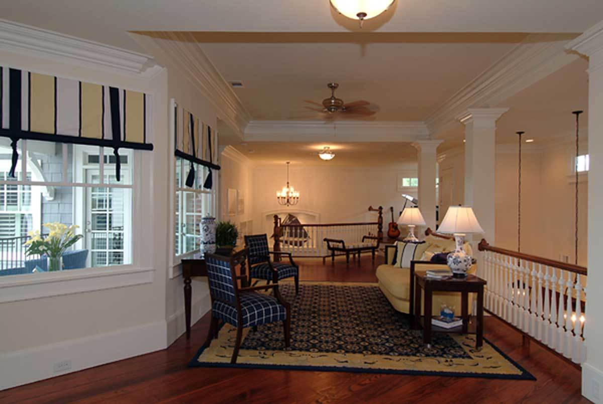 The social room is filled with dark wood tables, beige sofa, cushioned bench, blue checkered armchairs, and a large area rug.