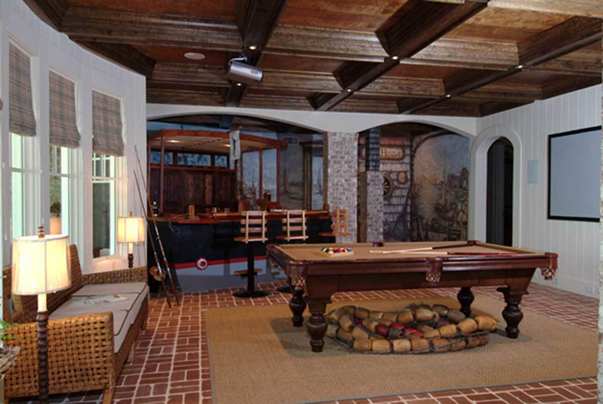 Game room with a billiard table, wicker sofa, and a wet bar paired with wooden counter chairs.