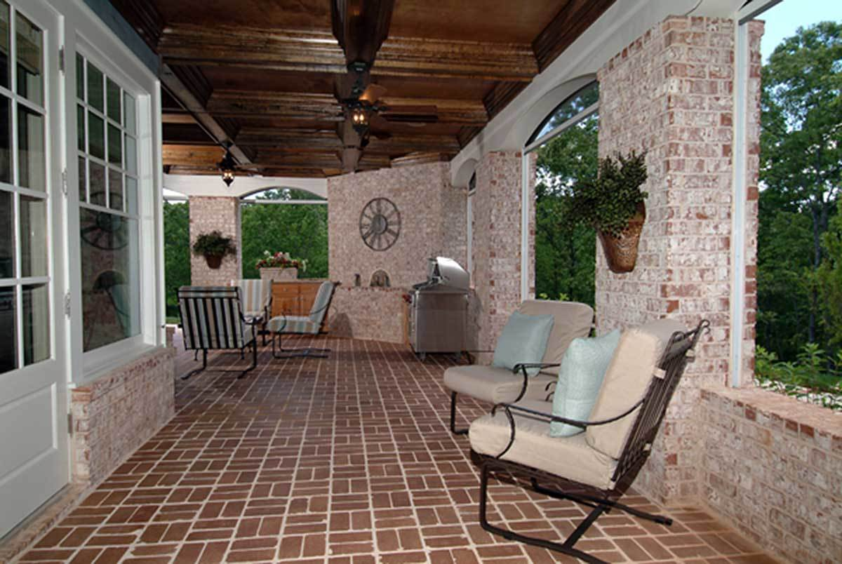 Covered patio with a summer kitchen, cushioned seats, and large arched windows fitted on the stone brick walls.