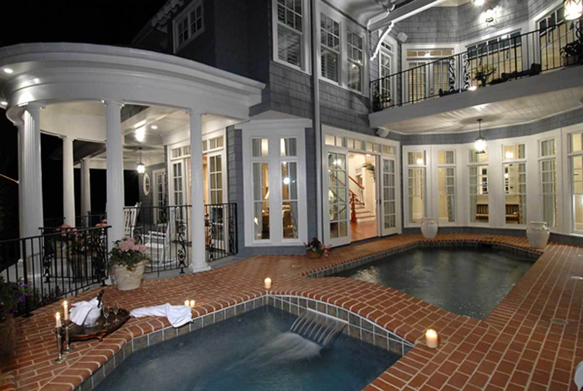 Home's lanai featuring an in-ground pool and a hot tub separated by a red brick bridge.