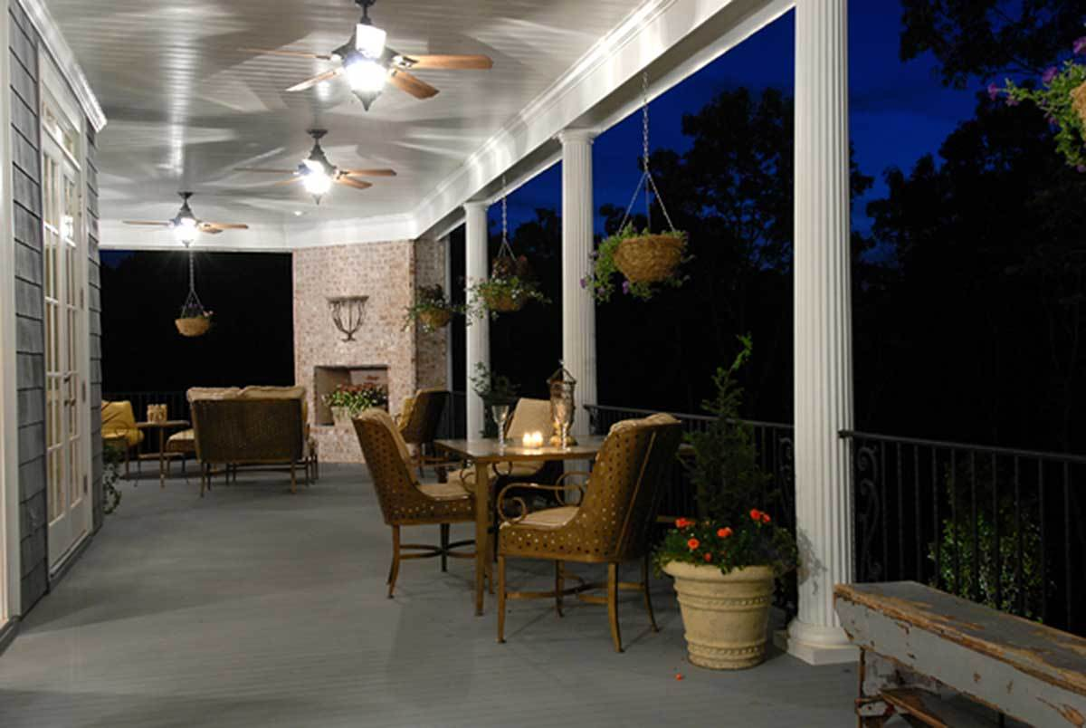 Covered patio with wicker chairs, a corner fireplace, hanging plants, decorative columns, and multiple ceiling fans.