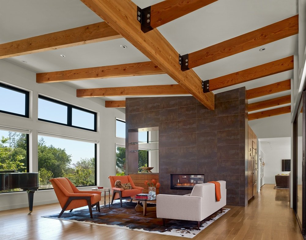 The living room area has a tall arched ceiling with exposed wooden beams. You can also see a large stone wall that houses the fireplace across from the sofa set.