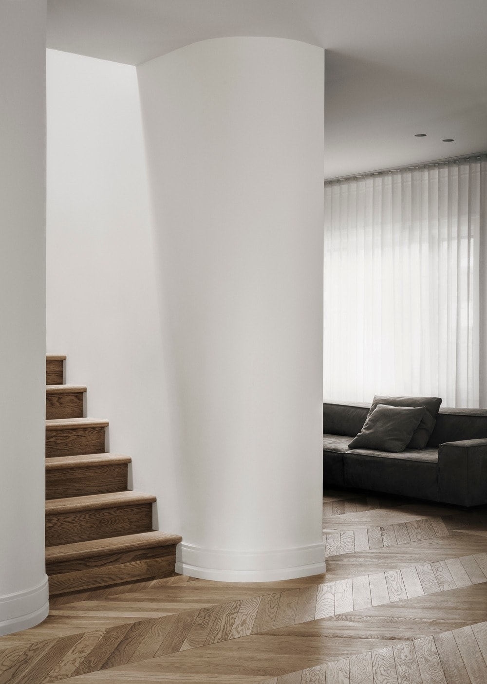 This is a look at the family room from the hall that leads to the staircase that has wooden steps to match the floor.