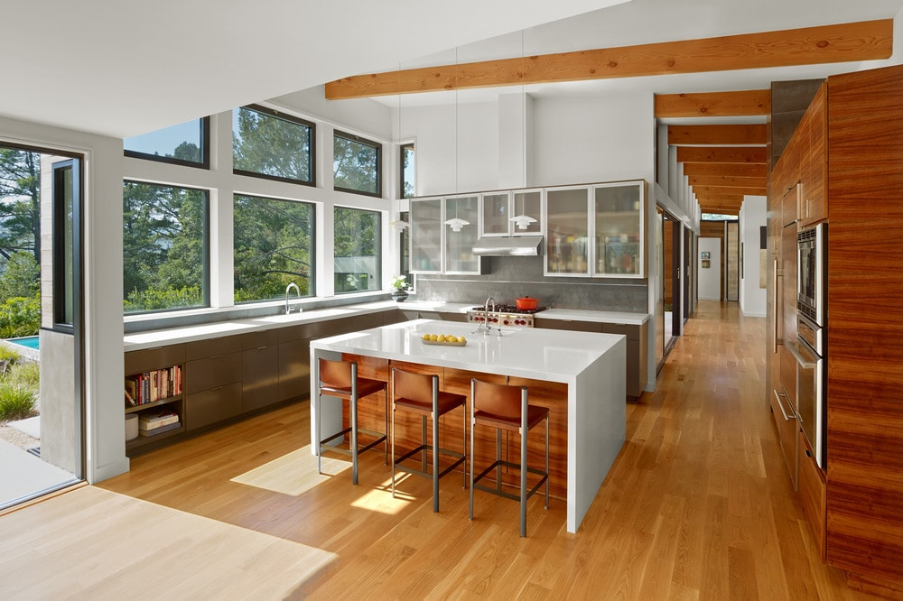 The kitchen is bathed in sunlight from the large glass windows on one side. This complements the bright waterfall kitchen island paired with stools for a breakfast bar.