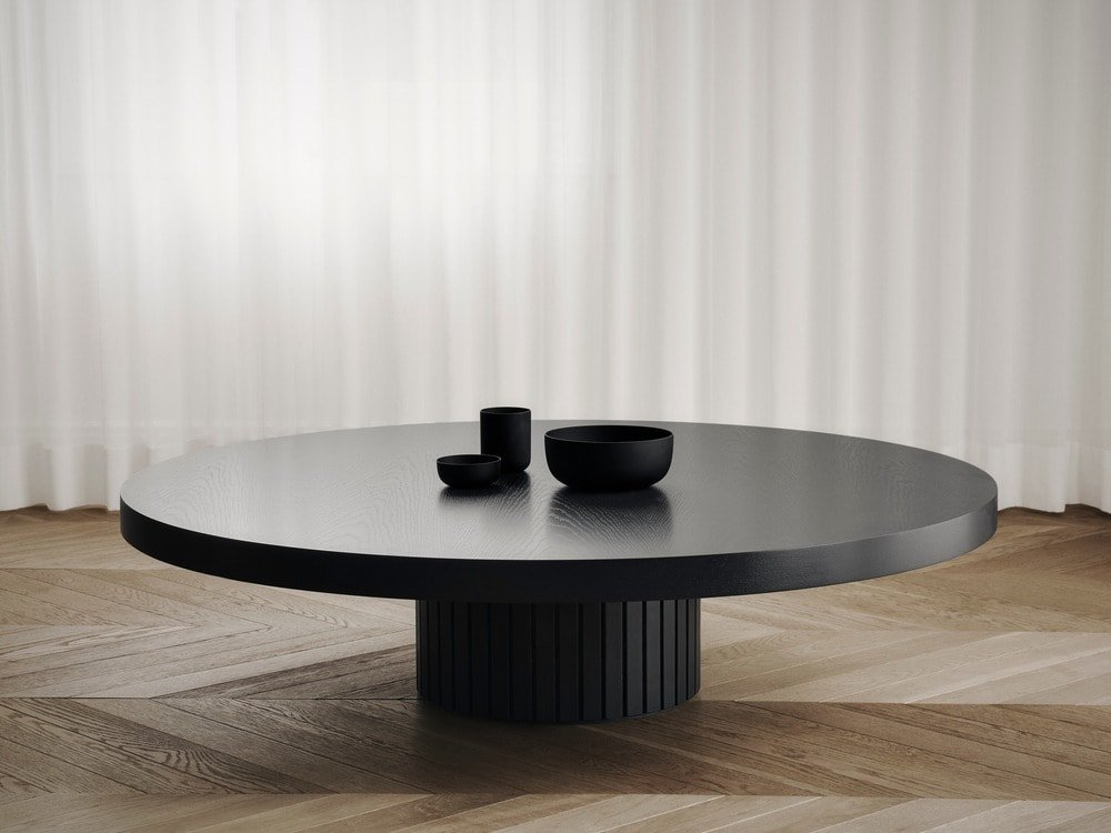 In between the fireplace and the large curved sofa is this black round coffee table that matches well with the black sofa.
