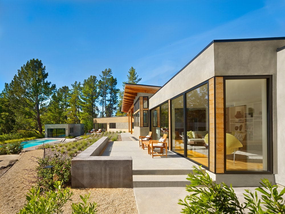 This is a look at the back of the house with a pool area. You can see the large glass walls of the house complemented by large concrete walkways and shrubs.