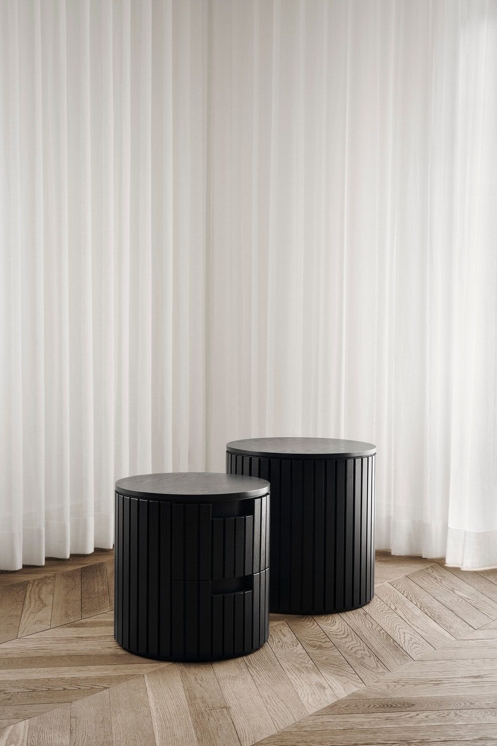 At a far corner of the living room is a couple of black stoops that stand out against the bright curtained windows.