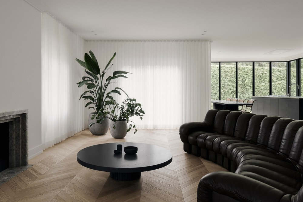 On the side of the piano is a large black curved sofa that stands out against the light hardwood flooring.