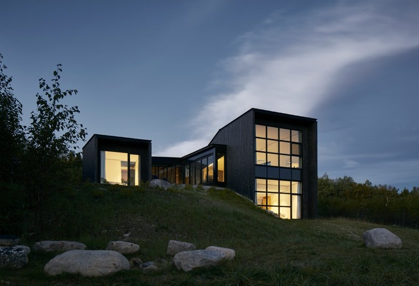 This is a view of the house with sleek black exterior walls that are complemented by the large glass walls that glow warmly from the interior lights.
