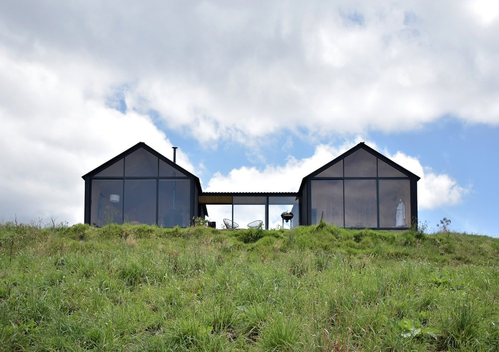 This house has two structures connected by a hallway with glass walls. These glass walls are paired well with the black exteriors.