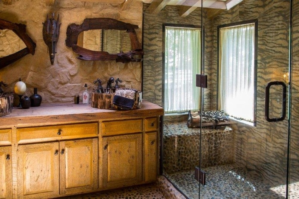 This is a look at the wooden vanity with a freestanding sink and a mirror above. On the side of this is the glass-enclosed shower area. Image courtesy of Toptenrealestatedeals.com.