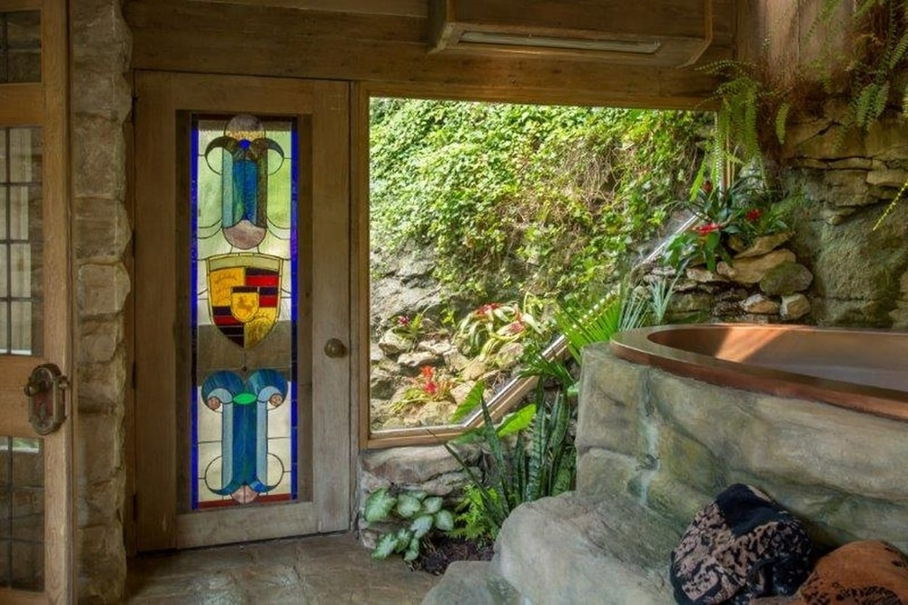 This bathroom has a stained glass panel on its door. On the side of this is the large stone structure that houses the bathtub. Image courtesy of Toptenrealestatedeals.com.