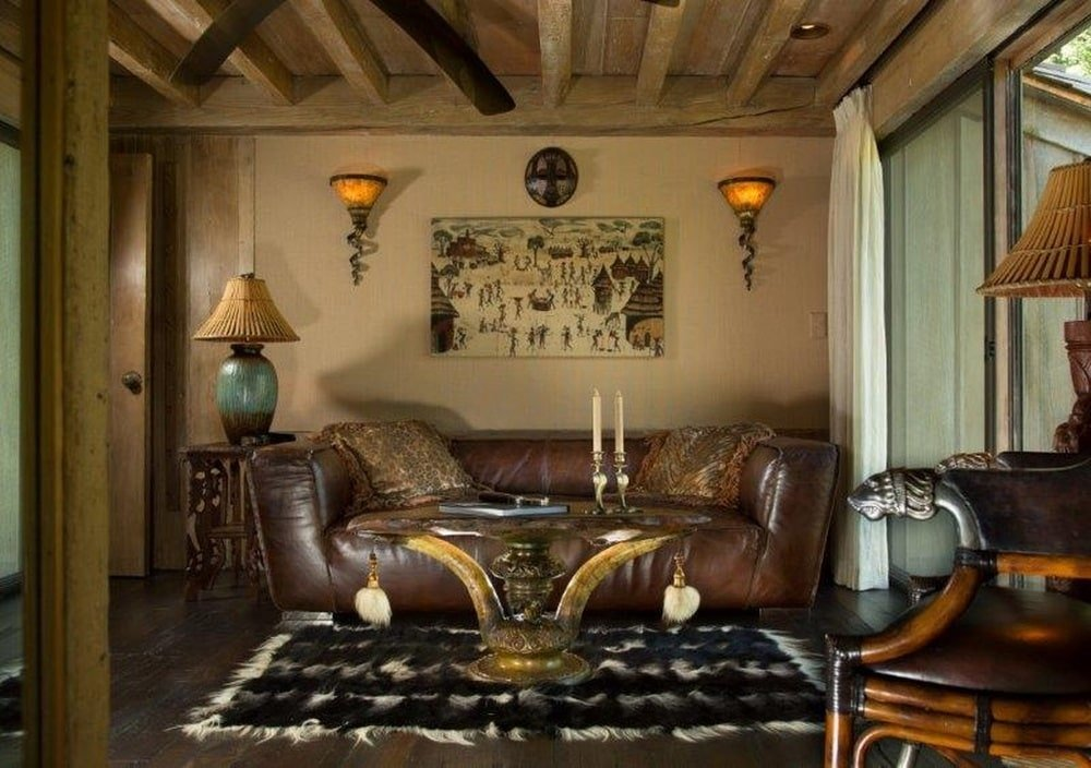 This is the den with a large dark brown leather sofa topped with a beige ceiling with exposed beams. Image courtesy of Toptenrealestatedeals.com.