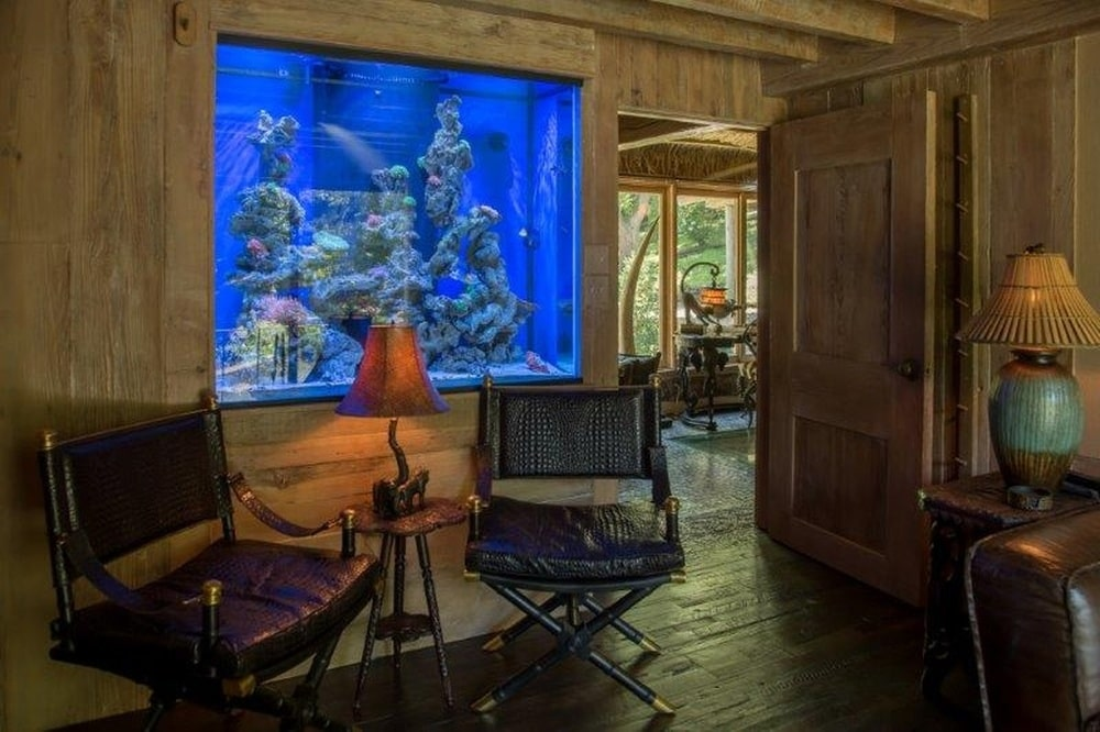 On the side of the brown leather sofa of the den is this small area by the door with a large aquarium above a couple of armchairs. Image courtesy of Toptenrealestatedeals.com.