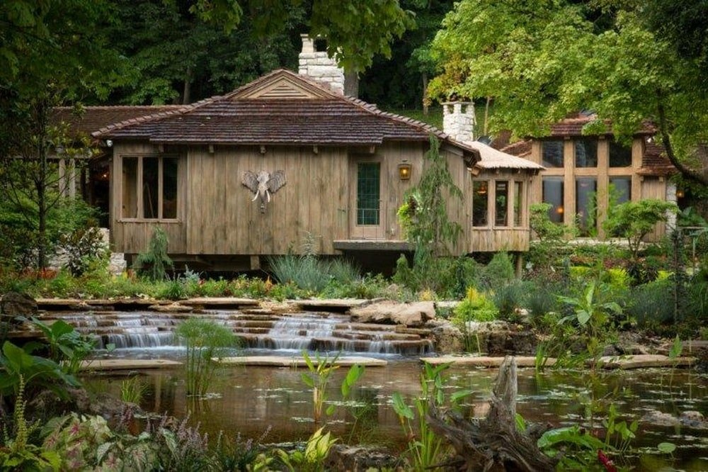 This is a look at the back of the house from the vantage of the water scenery. This side shows more of the wooden exterior walls that fit the green landscape surrounding it. Image courtesy of Toptenrealestatedeals.com.