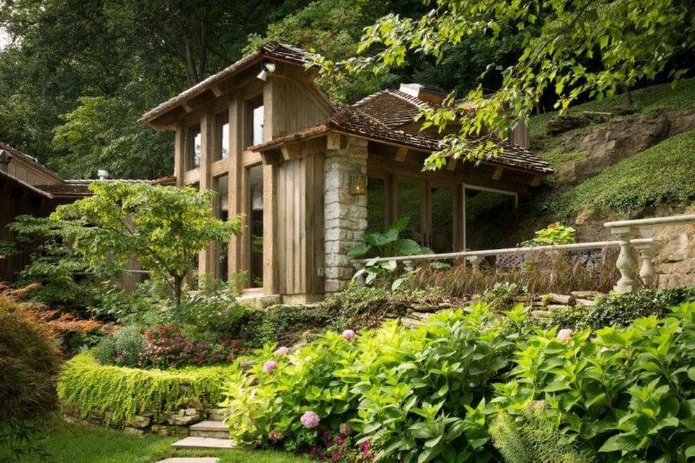 This is the detached guest house with tall glass walls and surrounded by a jungle of trees. Image courtesy of Toptenrealestatedeals.com.
