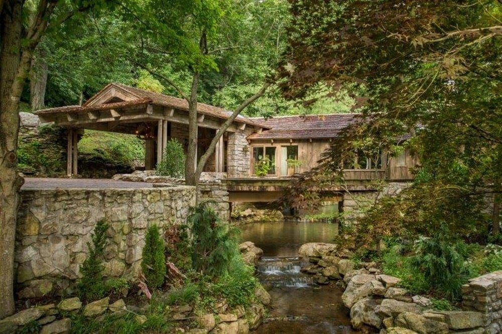This is a look at the other side of the house that also has a water scenery adorned with tall trees and shrubs on the side. Image courtesy of Toptenrealestatedeals.com.