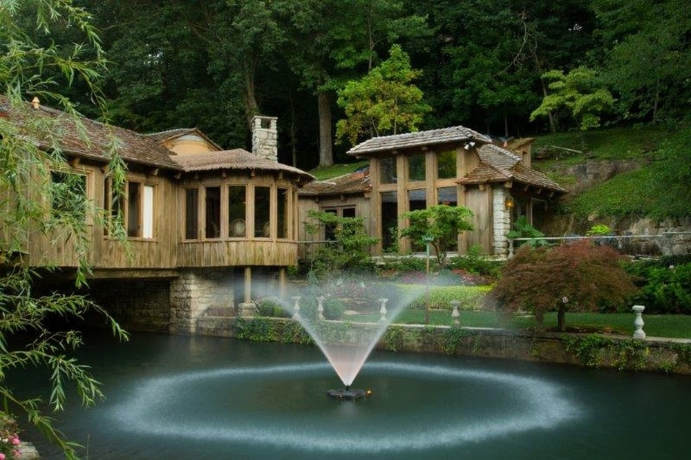 This is a look at the house with a foreground of the fountain. You can see here the wooden exteriors of the house complemented by tall glass walls and the background of tall trees. Image courtesy of Toptenrealestatedeals.com.