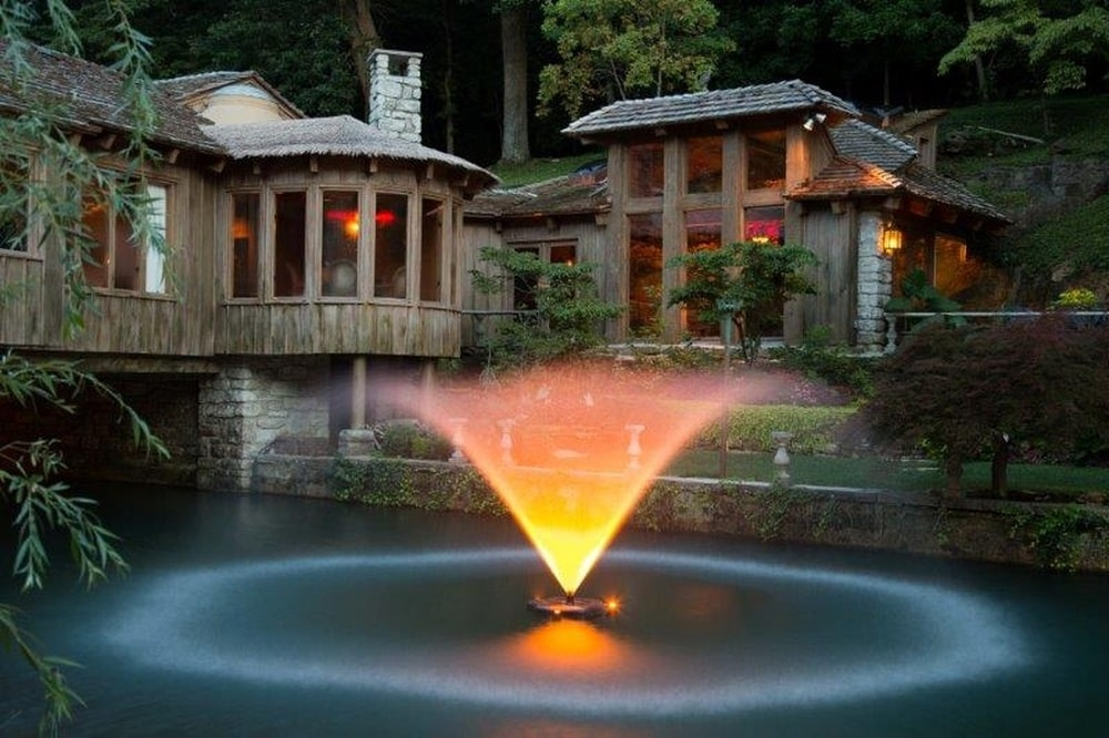 This is a nighttime view of the fountain showcasing the ethereal glow to match the warm glow of the house. Image courtesy of Toptenrealestatedeals.com.