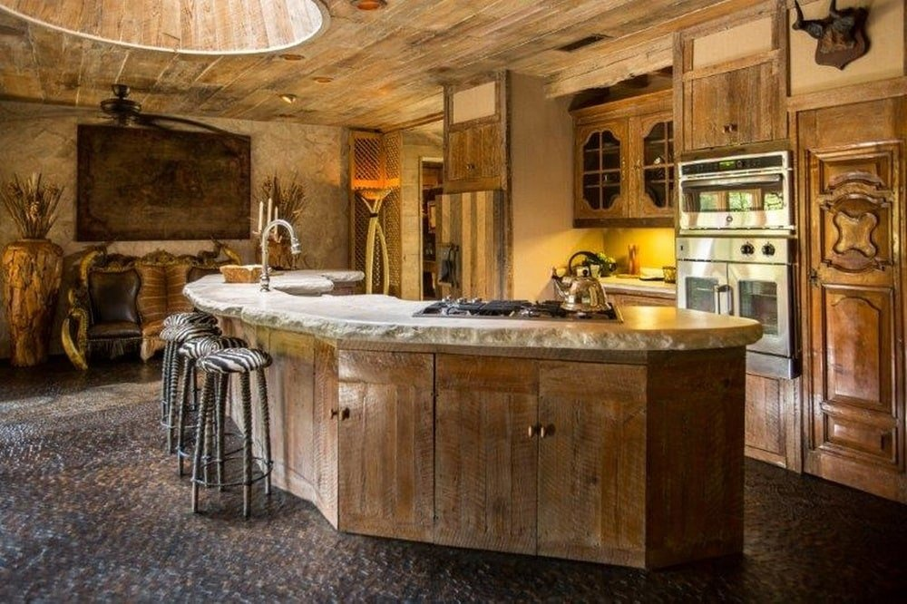This is the kitchen with a large curved kitchen island with a wooden hue that matches with the wooden cabinetry of the cooking area. Image courtesy of Toptenrealestatedeals.com.