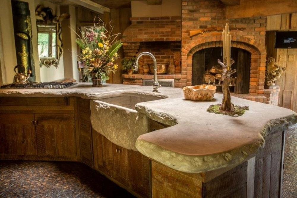 This is a closer look at the large curved kitchen island with a rustic rough-cut design to its stone countertop that extends to the deep sink. Image courtesy of Toptenrealestatedeals.com.