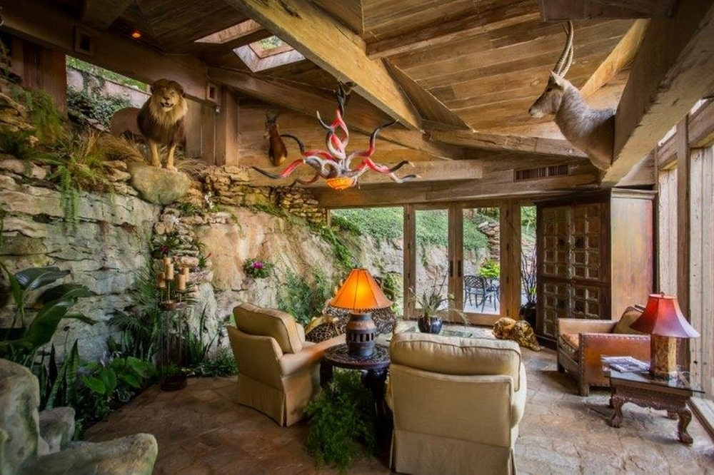 The living room has a set of beige sofas and armchairs paired with a rustic stone wall and a wooden ceiling. Image courtesy of Toptenrealestatedeals.com.