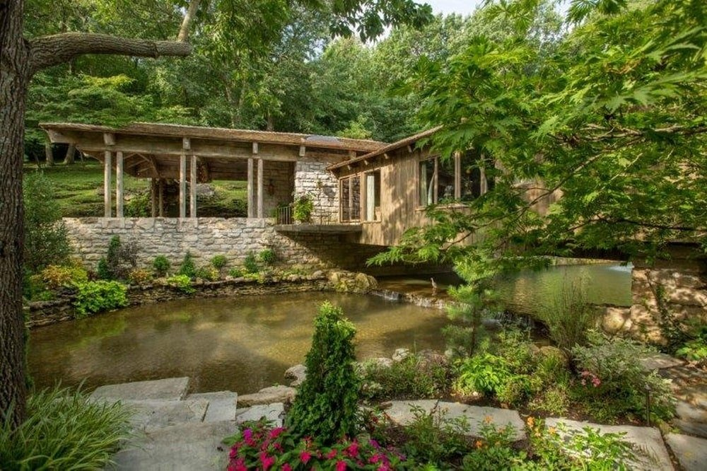 This is a close look at the pond that the house overlooks. This is surrounded by colorful flowering shrubs, decorative rocks and stone walls of the base of the house. Image courtesy of Toptenrealestatedeals.com.
