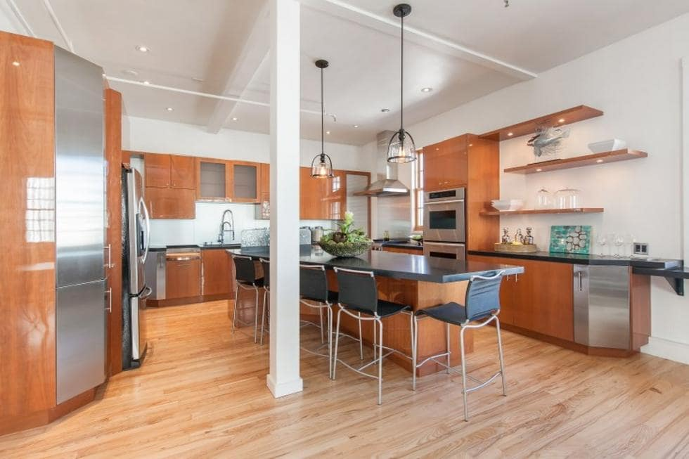 This is the kitchen at the far corner of the great room. It has dark wooden cabinetry on its walls to match the kitchen island and the hardwood flooring. You can also see here the thin pillar beside the kitchen island. Image courtesy of Toptenrealestatedeals.com.
