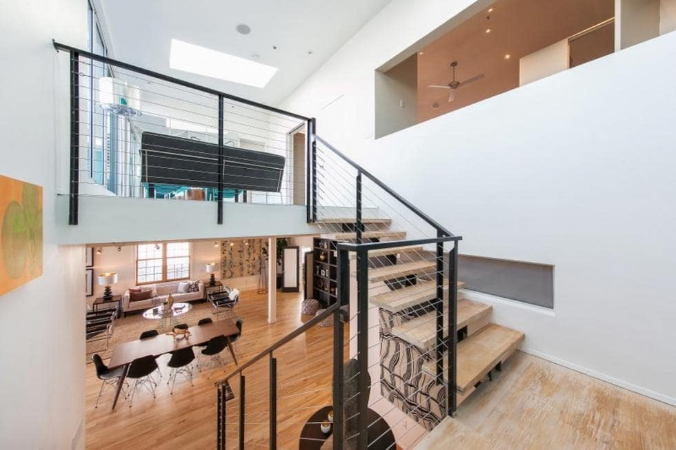 This is a look at the living room and the second-floor landing from the vantage of the stairs. This has light wooden steps that contrasts the black metal railings. Image courtesy of Toptenrealestatedeals.com.