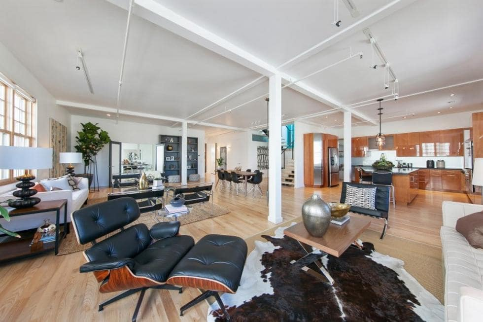 This is a look at the lounge area a few steps from the living room area. You can see here the black leather furniture that stands out against the bright white walls and ceiling. Image courtesy of Toptenrealestatedeals.com.
