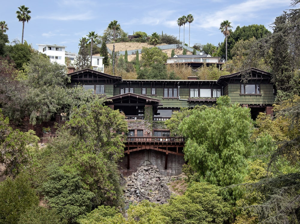 This is an aerial view of the back of the house looking over the cliff of Hollywood Hills. You can see here the dark tone of the house exterior walls complemented by the surrounding tall trees.