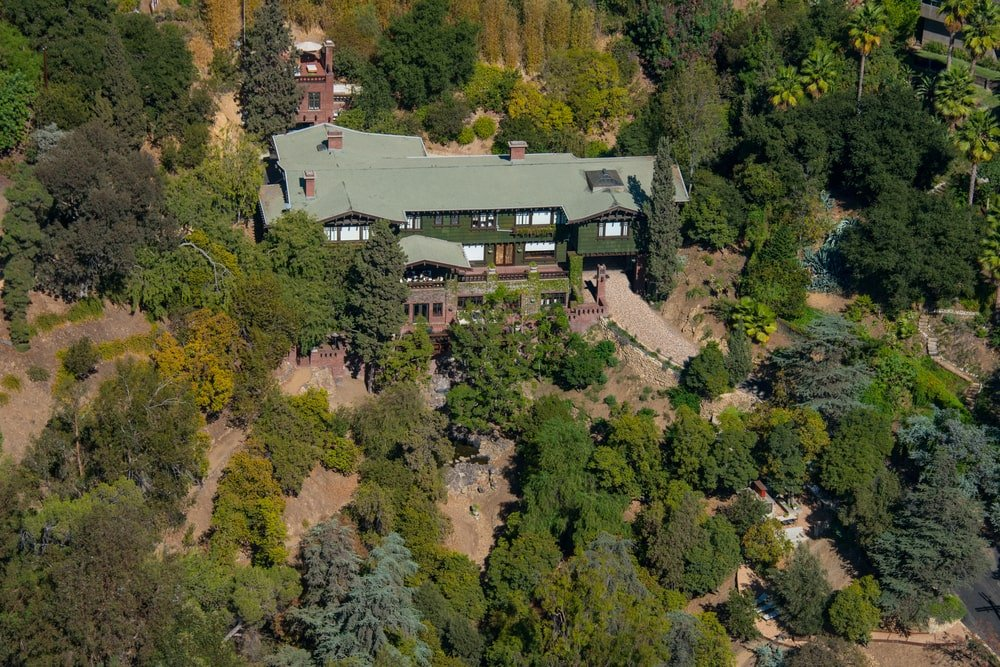 This is an aerial view of the house showcasing the dark tones of the house complemented by the surrounding landscape of tall trees and shrubs. Image courtesy of Toptenrealestatedeals.com.