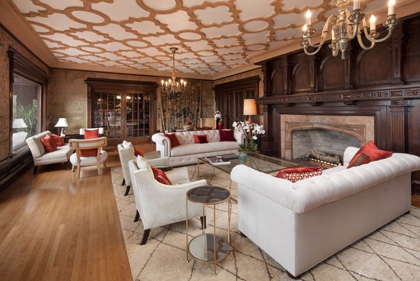 The spacious family room has two sets of light beige sofas on a patterned area rug that matches the patterns of the ceiling. These are then complemented by the large fireplace embedded into the wall with a dark wooden tone. Image courtesy of Toptenrealestatedeals.com.