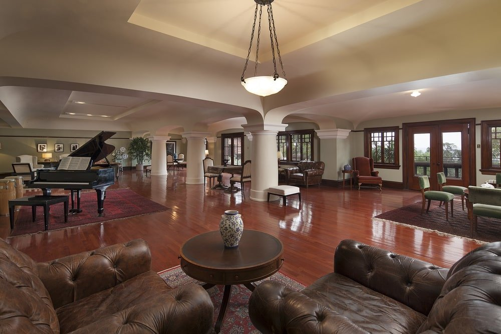 This spacious room has various sitting areas surrounding the music area with a large grand piano and a set of bongos. These are complemented by the dark hardwood flooring and the thick pillars. Image courtesy of Toptenrealestatedeals.com.