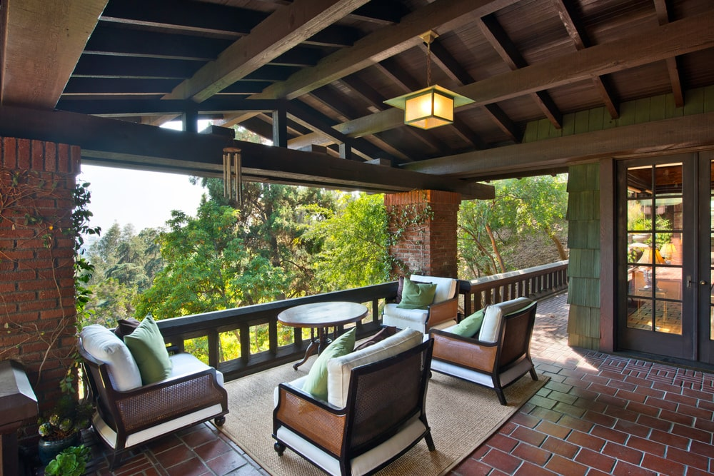 This is a look at one of the terraces with red brick flooring tiles and pairs of cushioned chairs under a wooden cathedral ceiling with exposed beams and pendant lights. Image courtesy of Toptenrealestatedeals.com.