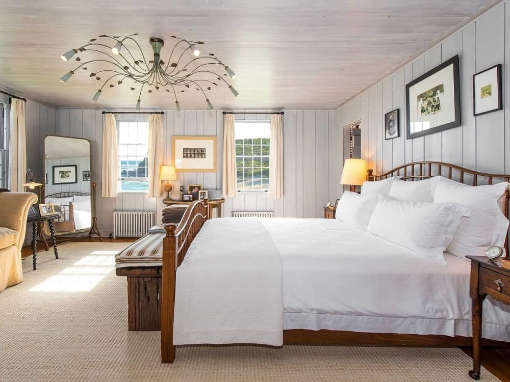 This bedroom has a wooden sleigh bed that matches the bench at the foot and the bedside tables. This is then topped with a large decorative chandelier. Image courtesy of Toptenrealestatedeals.com.