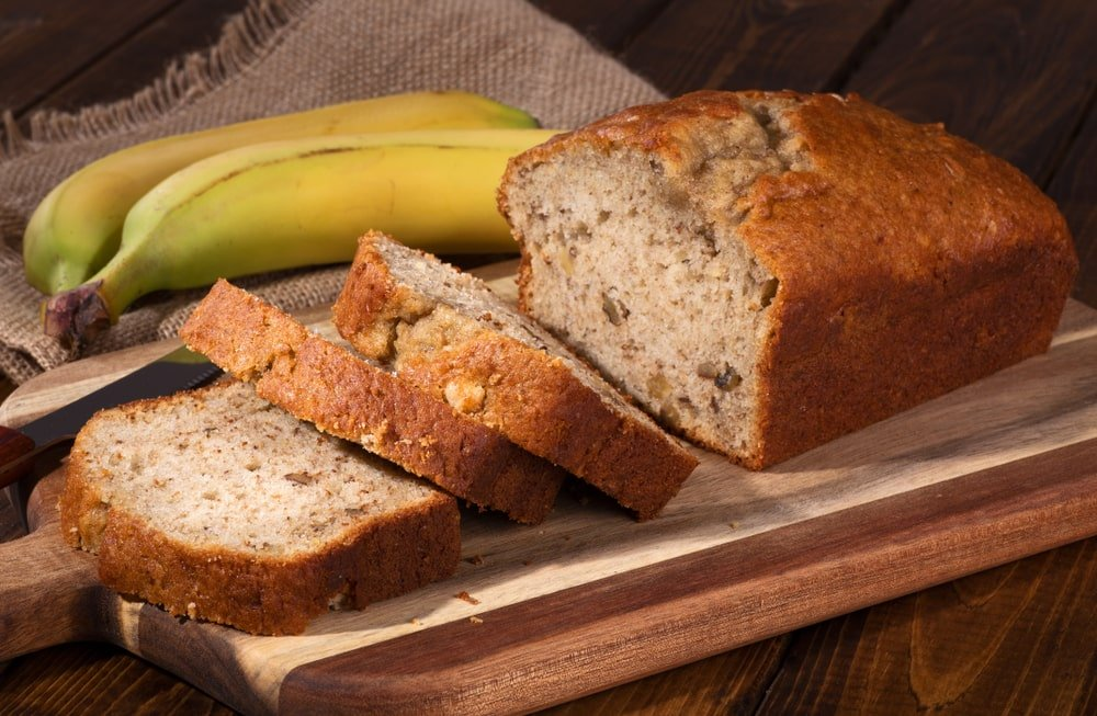 Sliced banana bread on a chopping board beside a pair of bananas on a wooden desk.