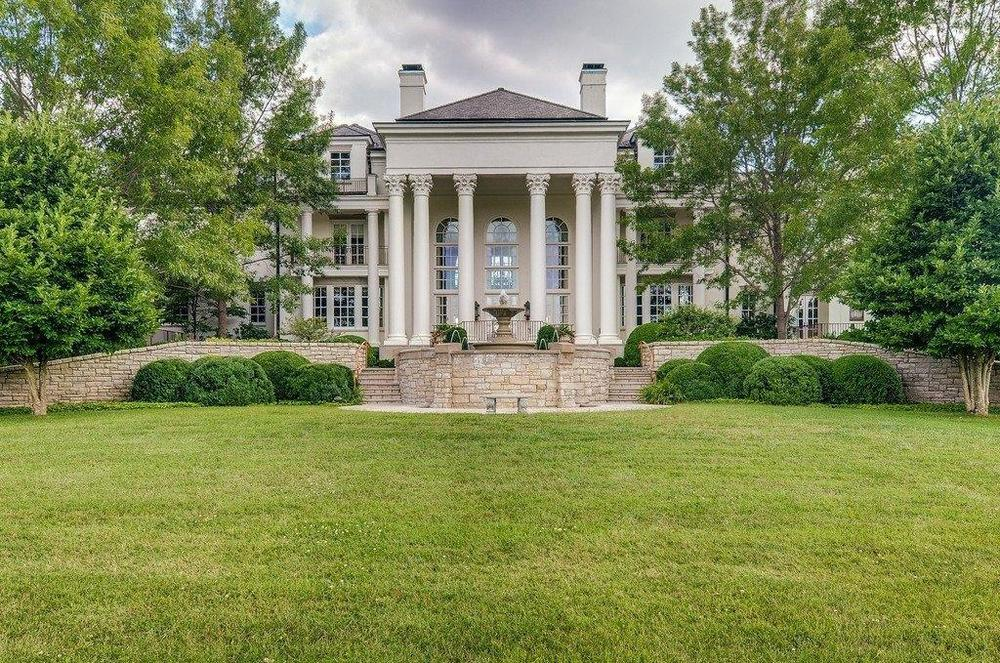 This is a look at the back of the house with tall pillars and a fountain complemented by the surrounding shrubs and tall trees. Image courtesy of Toptenrealestatedeals.com.