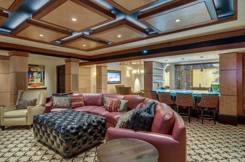 This is the bar area with a curved leather sectional sofa paired with a tufted ottoman on a carpeted floor. Behind the sofa is the glowing bar. Image courtesy of Toptenrealestatedeals.com.