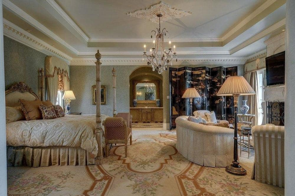 This bedroom has a beige patterned carpeting that matches with the sofa across from the four-poster bed. These are then topped with a chandelier from a tray ceiling. Image courtesy of Toptenrealestatedeals.com.