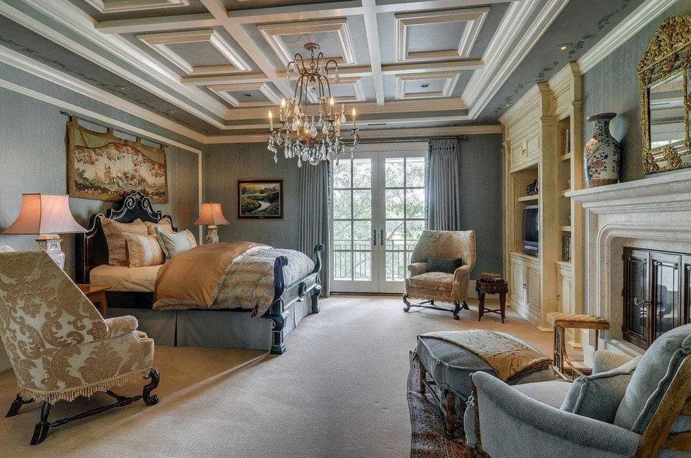 This bedroom has gray walls that match the coffered ceiling with a crystal chandelier in the middle over the bed. Across from the bed are built-in shelves and a fireplace. Image courtesy of Toptenrealestatedeals.com.