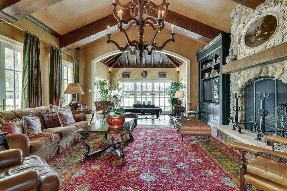 This family room has comfortable sofas and armchairs facing a wooden coffee table topped with a large chandelier. These are then warmed by the large fireplace on the other side. You can also see the game room at the far end. Image courtesy of Toptenrealestatedeals.com.