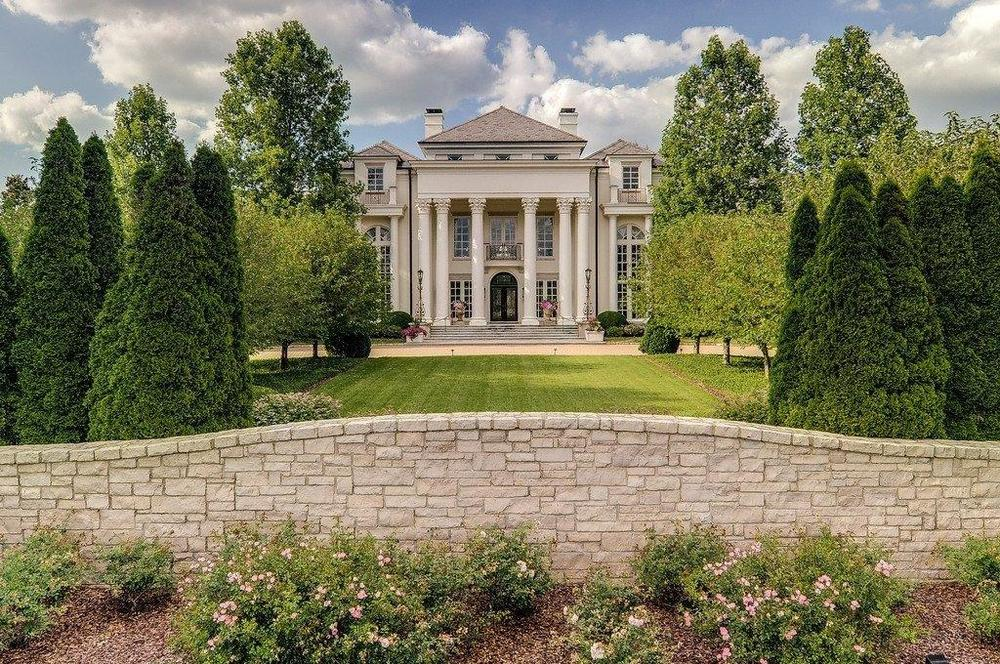 This is a front view of the mansion with its grand entrance adorned by tall white pillars. You can also see here the light tone of the exteriors complemented by the tall trees and large grass lawn. Image courtesy of Toptenrealestatedeals.com.