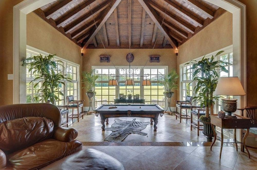 This is a look at the game room with a large pool table in the middle of glass walls and topped with a wooden arched ceiling with exposed beams. Image courtesy of Toptenrealestatedeals.com.