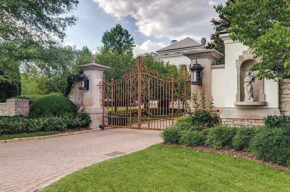 This is a look at the intricate iron main gate supported by two large concrete pillars with outdoor sconces. Image courtesy of Toptenrealestatedeals.com.
